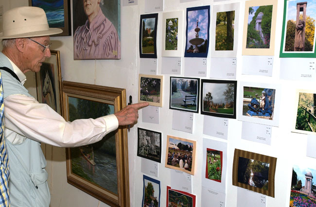 Gent looking at photograph entries on wall in Competition marquee